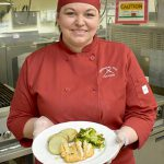 Woman is red chef's uniform holding food
